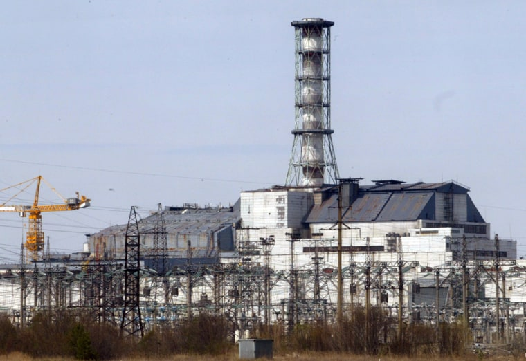 A chimney towers over the sarcophagus that covers destroyed Reactor No. 4, left, with Reactor No.3 on the right, at Ukraine's Chernobyl nuclear power plant on April 22, 2006.