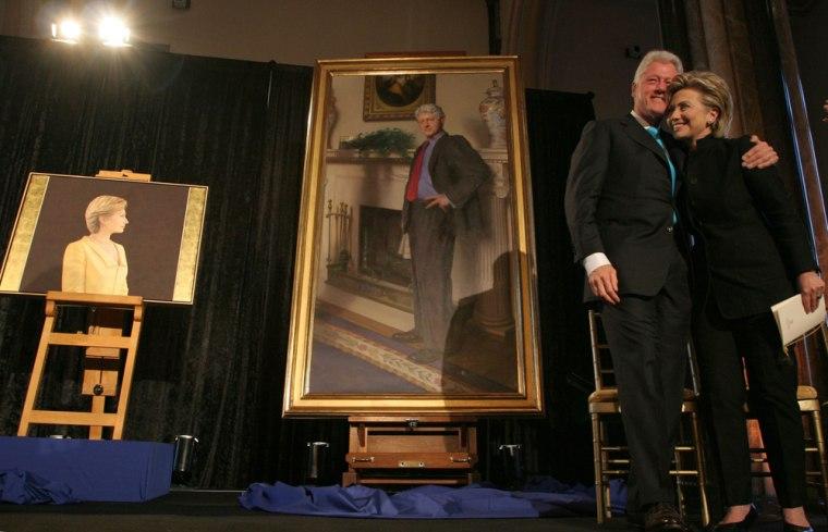 Former President Bill Clinton and Sen. Hillary Clinton (D-N.Y.) with their portraits.