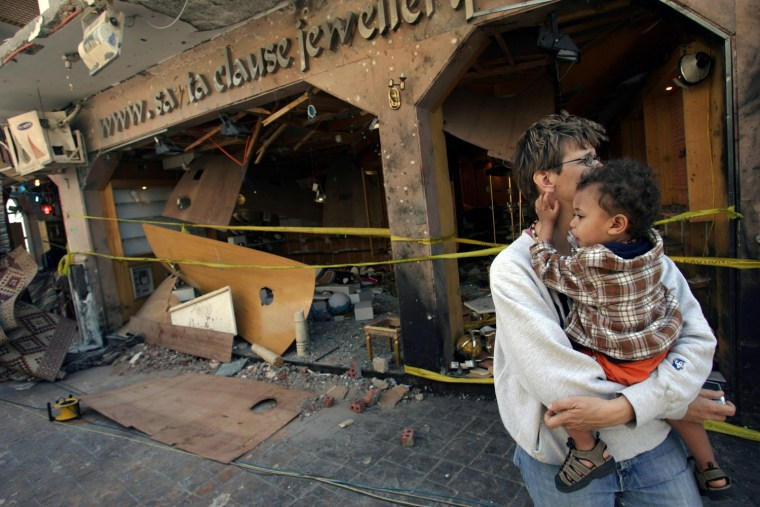 A tourist holds her son as they walk past a damaged store at one of the sites of the bombings at the Sinai seaside city of Dahab, Egypt, on Tuesday.