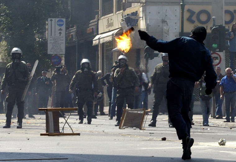 Protestors clash with riot police during