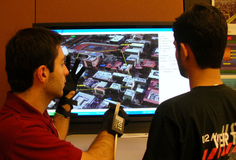 University of Southern California graduate student Jeff Khoshgozaran, at left,gestures with data gloves to zoom in on an area on the screen he wants to see in more detail. The glove interface is recognized by the Geospatial Decision Making database, or GeoDec.