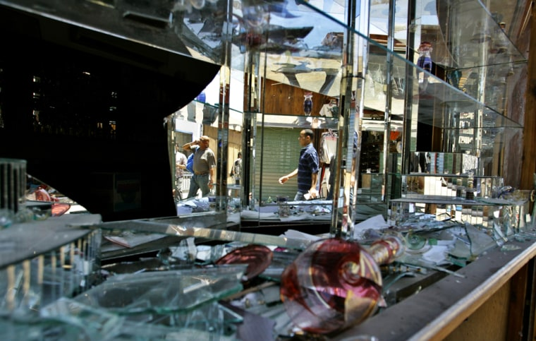 People pass a destroyed shop window on Wednesday in Dahab, Egypt, at the site where one of three bombs ripped through Egypt's Red Sea resort.
