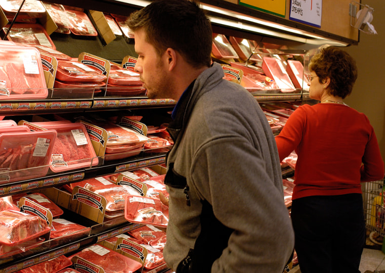 Dan Hogan, left, looks for a good cut of meat at the Cub Foods grocery store in Burnsville, Minn.