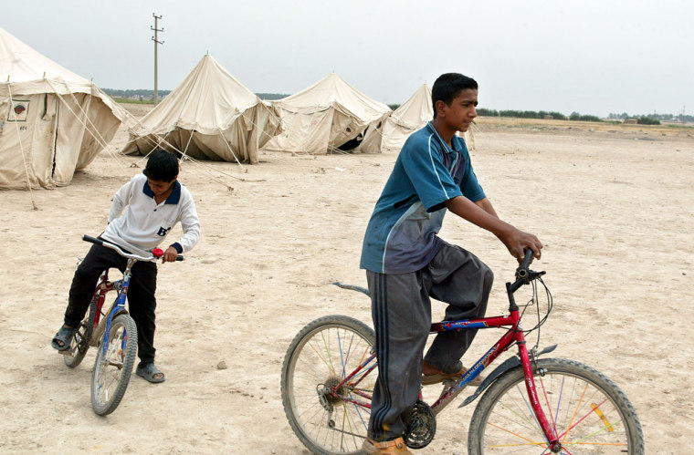 Iraqi boys ride bicycles in a camp in Ba