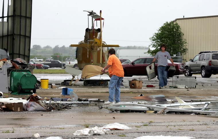 Bob Tharp, left, and Billy Tharpclean upafter high winds blew the doors off an airplane hanger at an airport in Gainesville, Texas, on Saturday.