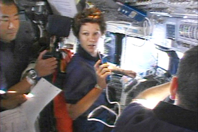 Japanese astronaut Noguchi, commander Collins and pilot Kelly work on the flight deck of the shuttle Discovery