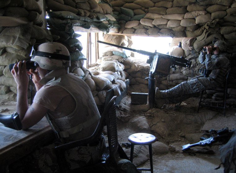Spc. Carlos Garcia, right, of Charlie Company, U.S. Army's 1st Battalion, 506th Infantry Regiment, looks through binoculars out a window of a U.S. observation post in Ramadi, Iraq, in this March 30 photo.