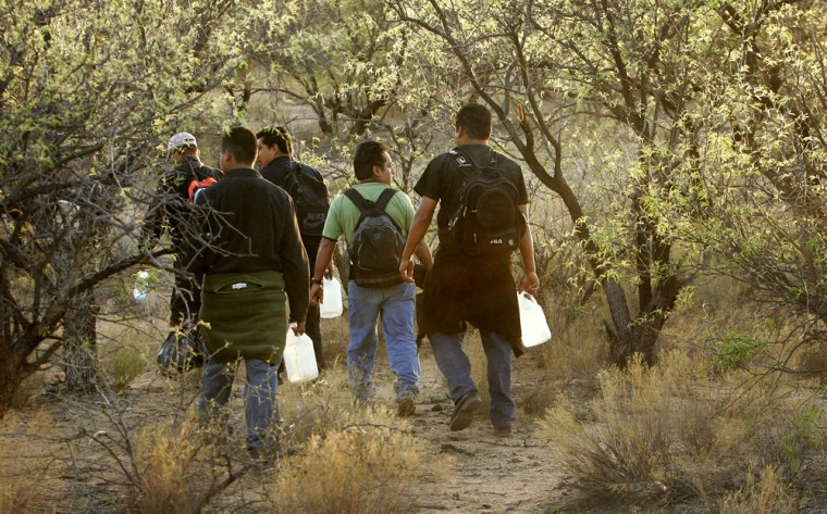 Migrants walk with bottles of water shortly before nightfall as they cross the desert on Tuesday between Sasabe, Mexico, and Sasabe, Ariz. As temperatures rise, the U.S. Border Patrol and aid groups fear what could be one of the deadliest summers for migrants trying to enter the United States.