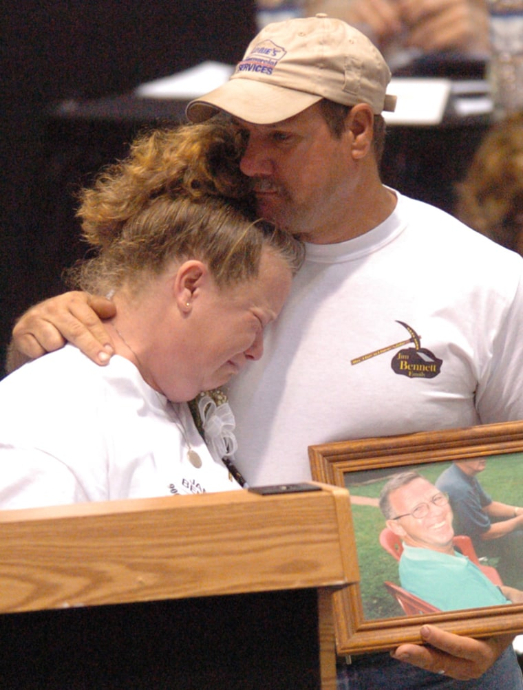 Ann Merideth, daughter of deceased miner James Bennett,cries onher husband, Dan, while holding a photo of her fatherat West Virginia Wesleyan College during the first day of the Sago Mine disaster hearings onTuesday.