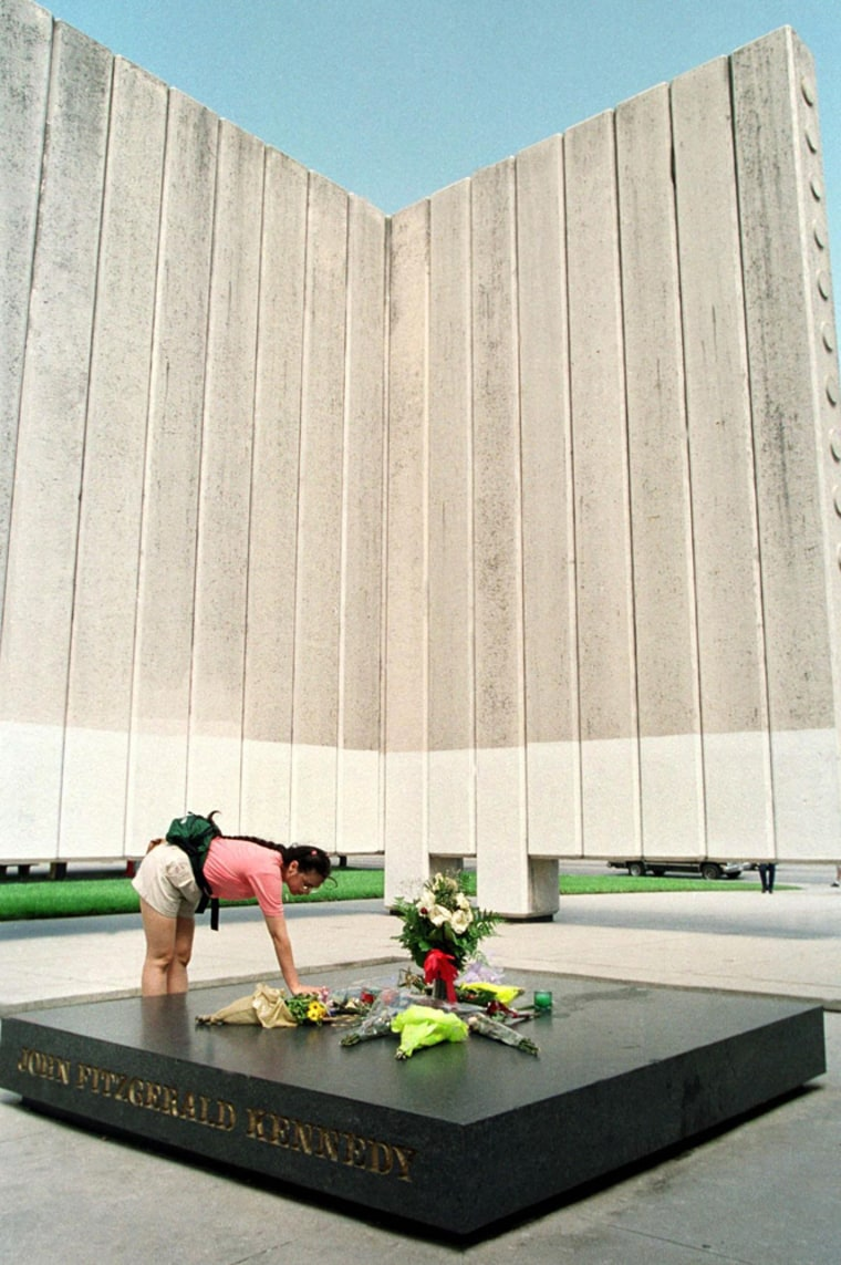 A woman lays flowers on the memorial to assassinat