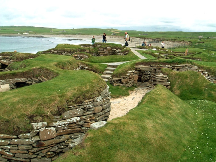 Visitors look at the 5,000 year-old remains of Skara Brae village in the Scottish Orkney Islands, July 19, 2005, which was revealed by a huge storm in 1850.