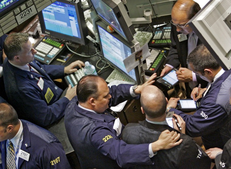 Traders crowd a post on the floor of the New York Stock Exchange Friday. The April jobs report hinted at a pause in interest rate hikes, driving the Dow Jones industrial average to a new six-year high.