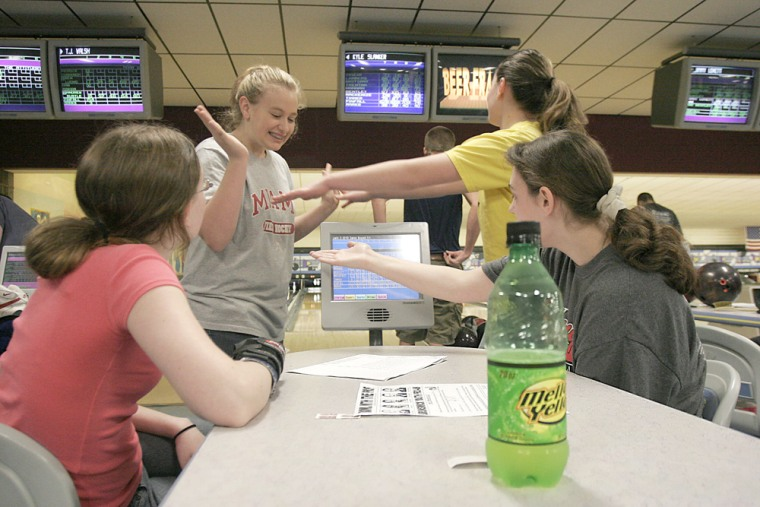 Centerville High School student Mackenzie Timmons, 15, top left, gets a high-five from friends after bowling well in a game at Poelking Lanes in Dayton, Ohio. Teenagers are pumping new life into the bowling business and transforming the traditional bowling alleys into entertainment centers.