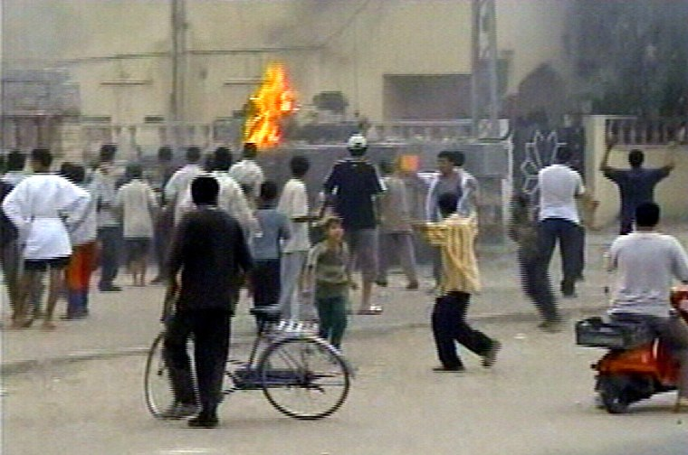 Crowds stand around and watch as others throw stones and Molotov cocktails at a British tank as it arrived on the scene where a British military helicopter crashed in Basra, Iraq, onSaturday in this image from TV.