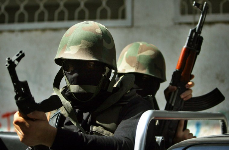 Masked militants of the al-Aqsa Martyrs' Brigades, a group linked to the Fatah movement, patrol an area around one of their offices after clashes with Hamas militants in Gaza City onTuesday.