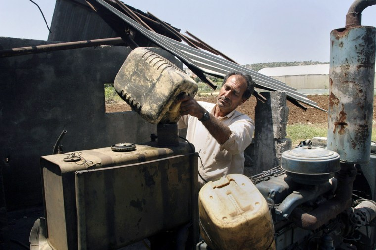 A Palestinian farmer on Wednesday uses his last can of fuel to fill up a generator that powers his watering systemin the West Bank town of Jenin.