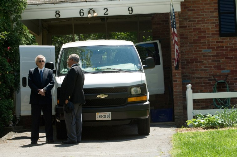 Federal authorities confer next to a van at the home of recently retired CIA official Kyle Foggo on Fridayin Vienna, Va.