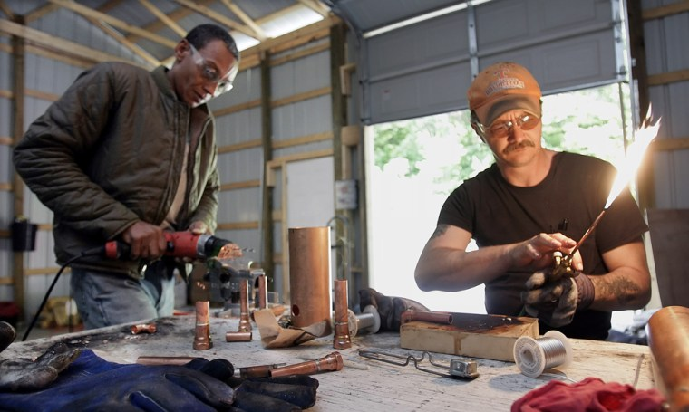 Randy Bumpus fires up a welding torch as he and Ralph White build a still at Dogwood Energy in Tullahoma, Tenn.