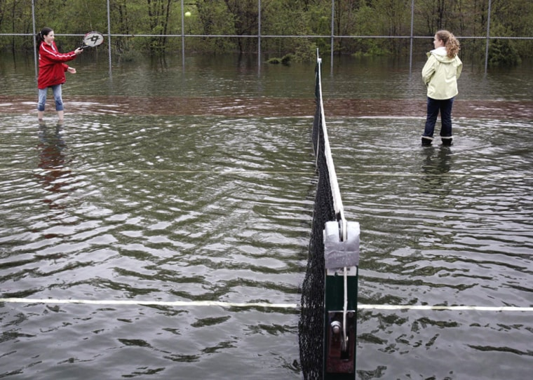 Thirteen-year-olds Justine Johnson and Allie Walsh play tennis in flooded tennis court in Melrose