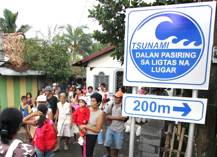 "Filipino villagers participate in the first-ever Pacific tsunami warning drill in the coastal village of Buhatan in Albay province, 210 miles (340 kilometers) southeast of Manila. The sign reads ""Tsunami: This Way to Safe Place."""