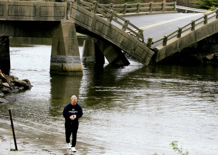 Local resident Pat Callinan walks by a collapsed bridge in Cape Neddick, Maine, on Tuesday. Southern Maine received a record amount of rain over the past week.