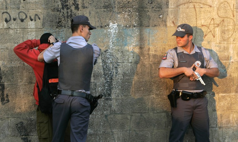 Police officers frisk a gang suspect Thursday at a checkpoint in Sao Paulo, Brazil.