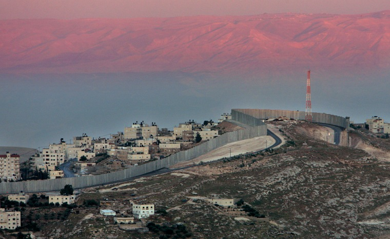 A section of Israel's separation barrier is seen on a hill between the West Bank village of Abu Dis and Jabel Mukaber on the edge of Jerusalem. As America contemplates construction of a massive fence along the Mexican border, it can look to Israel as a test case.