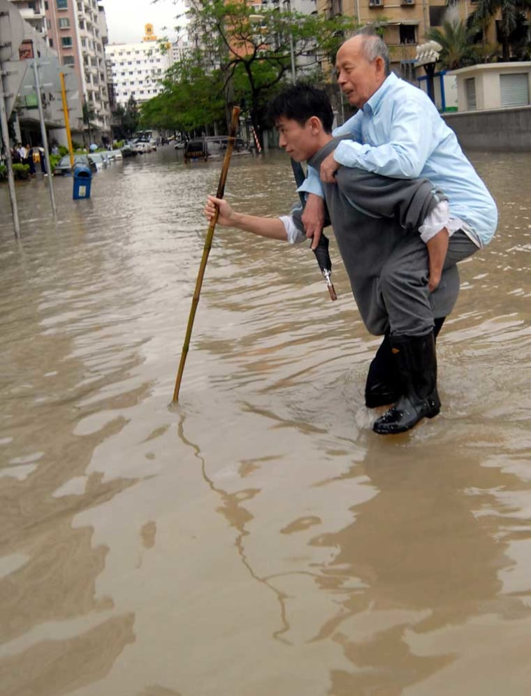 A young man helps an elderly manacross a flooded street after heavy rain from Typhoon Chanchu in Xiamen, China,on Thursday.