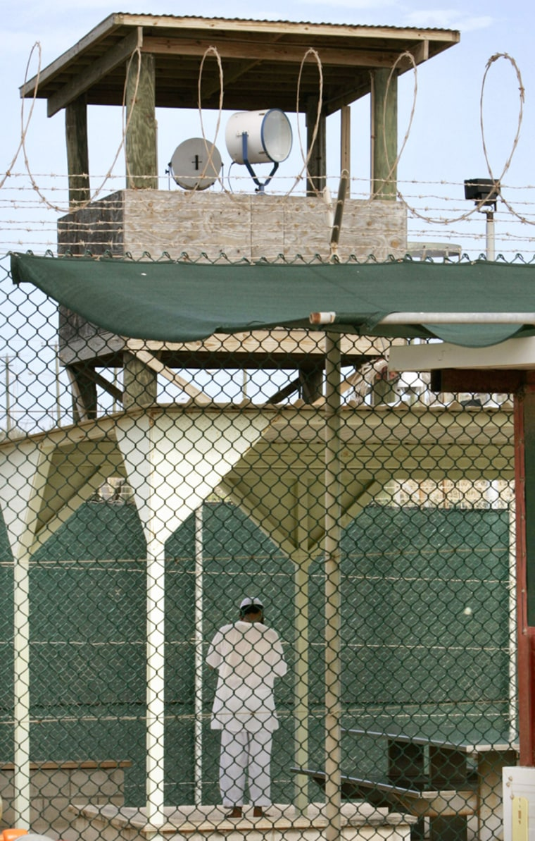 An unidentifiable detainee spends time outside his cell in the Guantanamo Bay Naval Station, Cuba, on July 6, 2005.