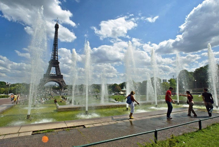 Residents and tourists refresh in the Trocadero fountains in July in Paris.