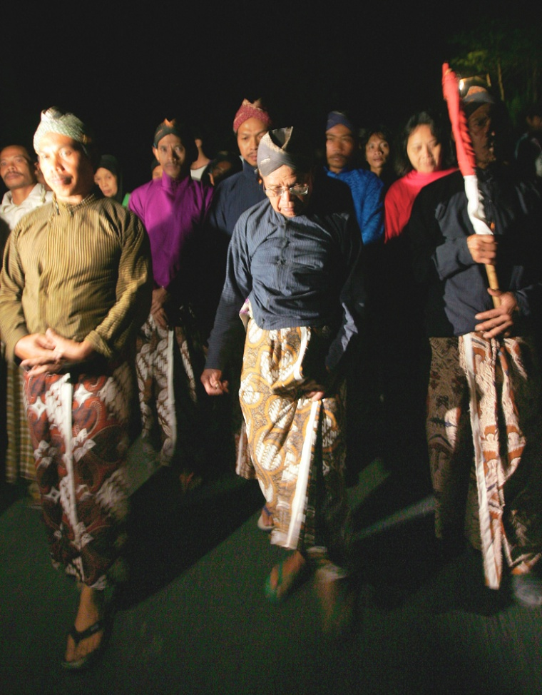 Wearing traditional dress, Maridjan, center, the spiritual guardian of Mount Merapi, and other villagerscircle their village late Thursday night as a part of aprayer for protection from the rumbling volcano.The men later asked journalists to leave and it was reported that they removed their clothes as part ofthe ritual.