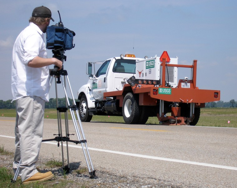 "A cameraman videotapes a ""vibe truck"" moving along an Arkansas highway on May 16 to measure sediment in the area for evidence of past earthquakes in the New Madrid seismic zone."