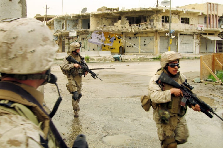 U.S. Marines from the 3rd Battalion, 8th Marine Regiment's Kilo Company run across a war-battered road to avoid snipers on their way back to a base in Ramadi, Iraq, last month.