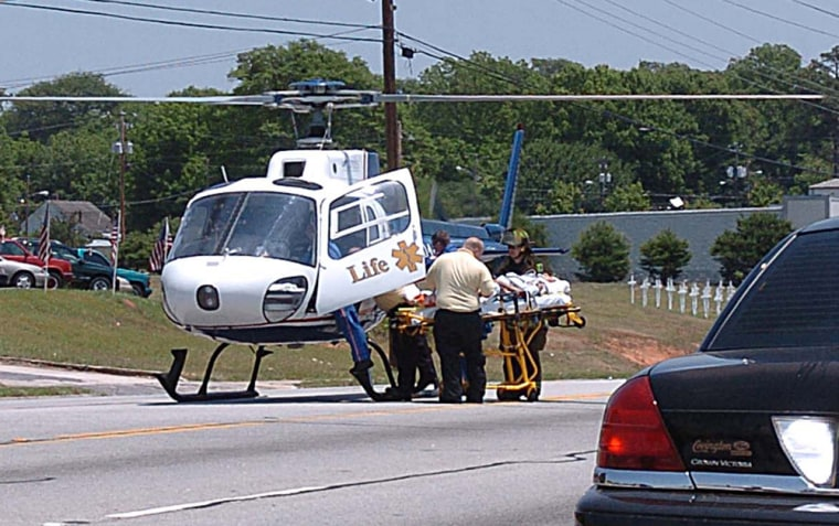 One of thevictims of the incident in the parking lot of an McDonald's restaurant in Covington, Ga. is airlifted Tuesday for transport to a hospital.