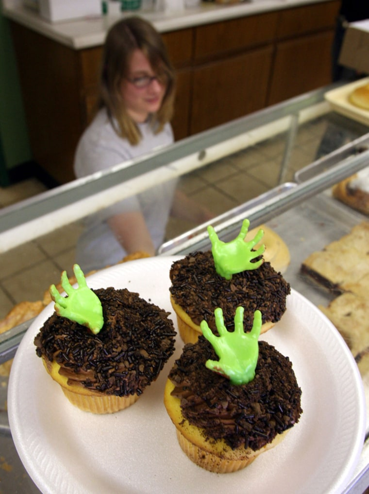 Cashier Laura Hosbach, prepares an order for a customer at The Milford Baking Co. in Milford, Mich., earlier this week.The store has been raking in the dough selling spooky snacks as investigators dig upa local farm seeking the remains of Teamsters boss Jimmy Hoffa.