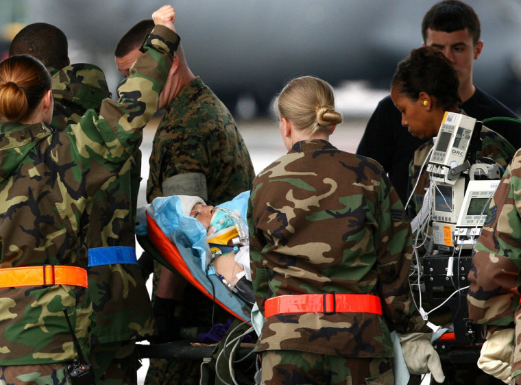 US Air Force medical personnel carry CBS correspondent Dozier into an ambulance bus at Ramstein airbase