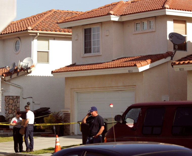 Garden Grove, Calif. police stand outside a home Wednesday where officers found three dead people and an unharmed baby girl. Police had no suspects in the deaths.