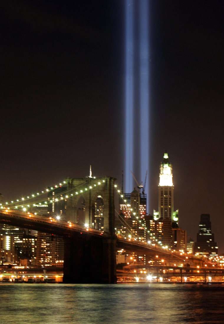September 11 Tribute in light tower above the Brooklyn Bridge and New York city skyline