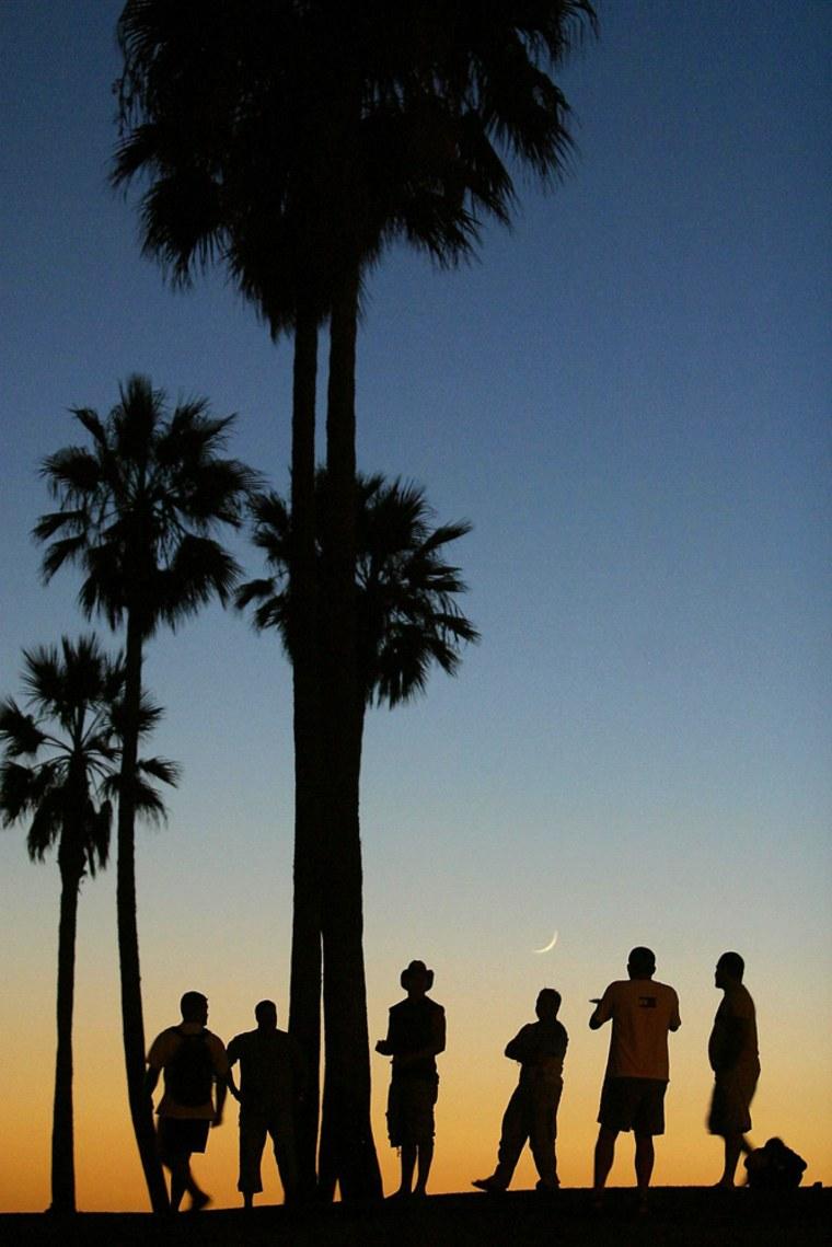 A group of men enjoy the sunset on Venice Beach in Venice, California.