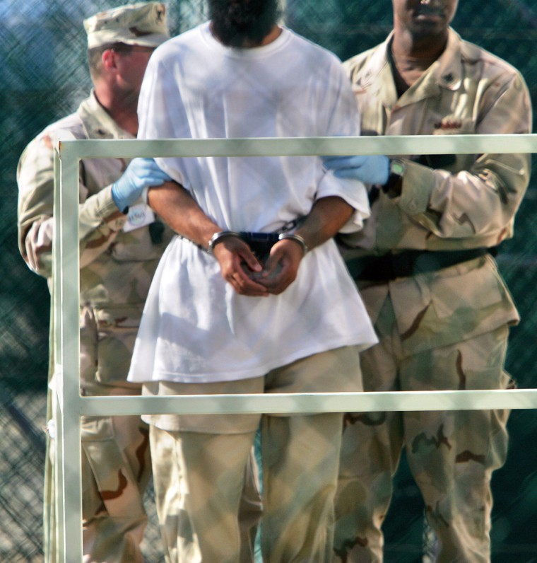 U.S. military personnel transport a detainee into a building within the grounds of the maximum security prison at Camp Delta 2 & 3 at the Guantanamo Bay U.S. Naval Base, Cuba. More Guantanamo Bay detainees have joined a hunger strike, raising the number of those refusing food to 89 from 75, the U.S. military said Thursday.