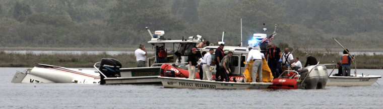 Rescue workers surround the wreckage of a small aircraft that crashed Friday, in Groton, Conn. Three people were pulled from Long Island Sound and two others were missing Friday after the plane went down in heavy fog about a half-mile short of the runway a Coast Guard spokeswoman said.
