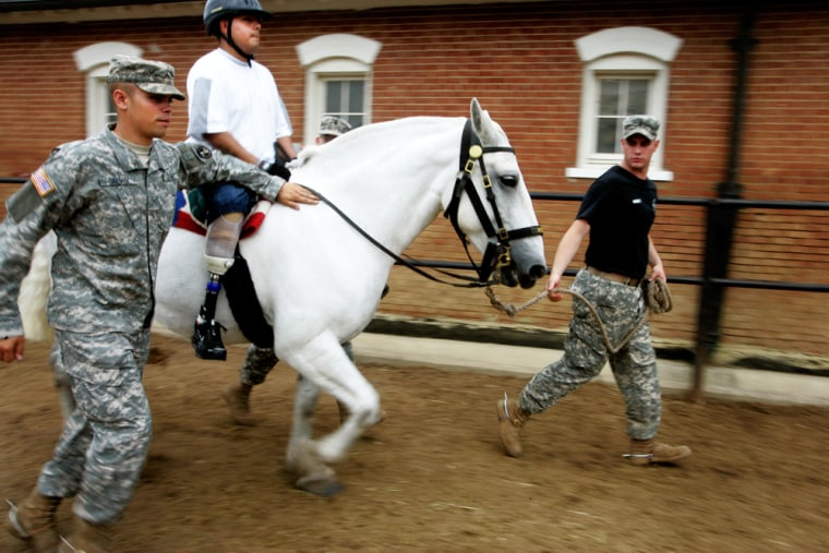 Army Sgt. Christian Valle, 23, from Hayward, Calif., who lost both his legs in Iraq, trots on a white Percheron horse, with the help of members of the 3rd Infantry Regiment (Old Guard), at the Caisson Stables at Fort Myer in Arlington, Va., on Friday.
