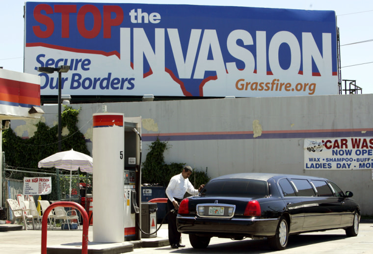 """A man in Miami fills uphiscar with gasMay 19under a new billboard calling on Americans to """"Stop the Invasion,"""" a billboard paid for by a conservative grass-roots advocacy group funded by local citizens who are frustrated with illegal immigration."""