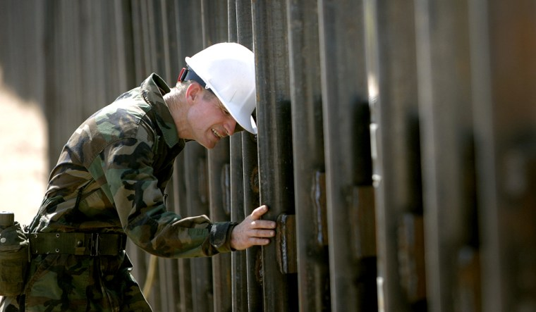 Utah National Guard soldier Sgt. David Cowley of the116th Construction Equipment Support Company examines a wall along the U.S. border in San Luis, Ariz., on Monday. Cowley is amongthe first 50 soldierssent to the borderas part of Operation Jump Start.