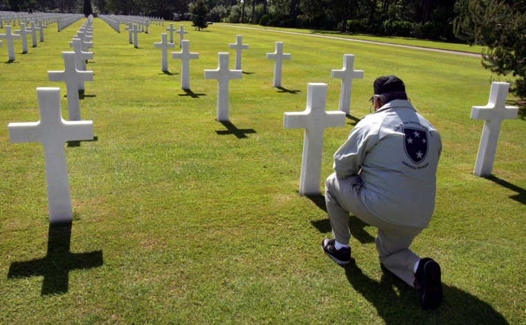 Robert Antuono of Providence, R.I., kneels in front of the grave of his brother-in-law Edward Di Falco, at the U.S. military cemetery at Colleville-Sur-Mer, France, onTuesday. Di Falco died on July 13, 1944, little more than a month after the D-Day invasion at Normandy.