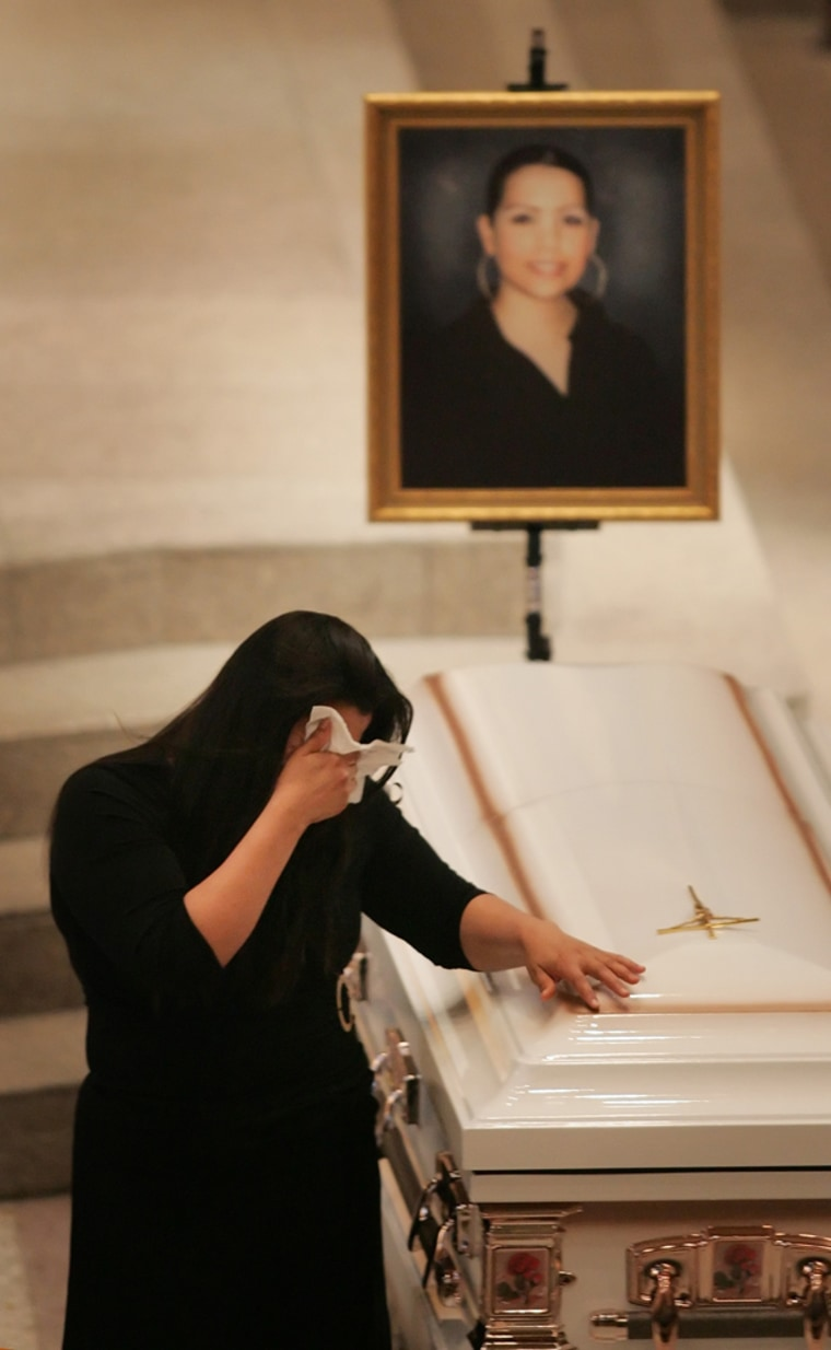 Santos Flores wipes her face Wednesday while in front of the casket of her niece, Flora Albarran, 22, before the start of a funeral for six of the seven victims of last week's slayings in Indianapolis.