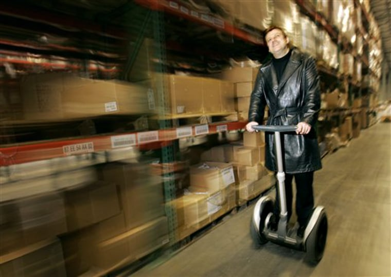 Overstock.com CEO Patrick Byrne travels down an aisle on his Go-ped scooter at his company's warehouse and distribution center in Salt Lake City. Byrne is fighting Wall Street sharks while trying to show he can turn a profit and build an enterprise to rival Amazon.com or eBay.