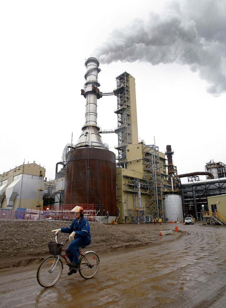 Worker rides bike near Syncrude's expansion mine, north of Fort McMurray