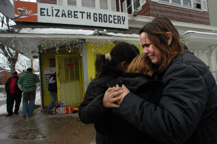 Telma Diaz, right, the aunt of shooting victim Enrique Perez, hugs her daughter Paloma Batista, left, and another woman, who is the sister-in-law of shooting victim Elizabeth Morel, in Hartford, Conn. The two victims were killed Jan. 5 during an armed robbery and shooting at Elizabeth Grocery.