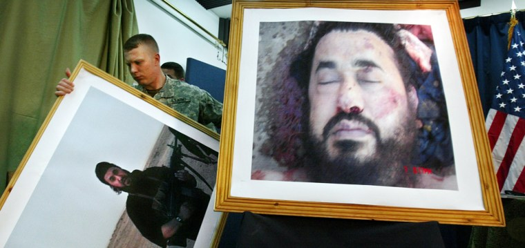 A U.S. soldier at a press conference in Baghdad takes down an older image of Abu Musab al-Zarqawi to display what the military said was a photo of him in death.